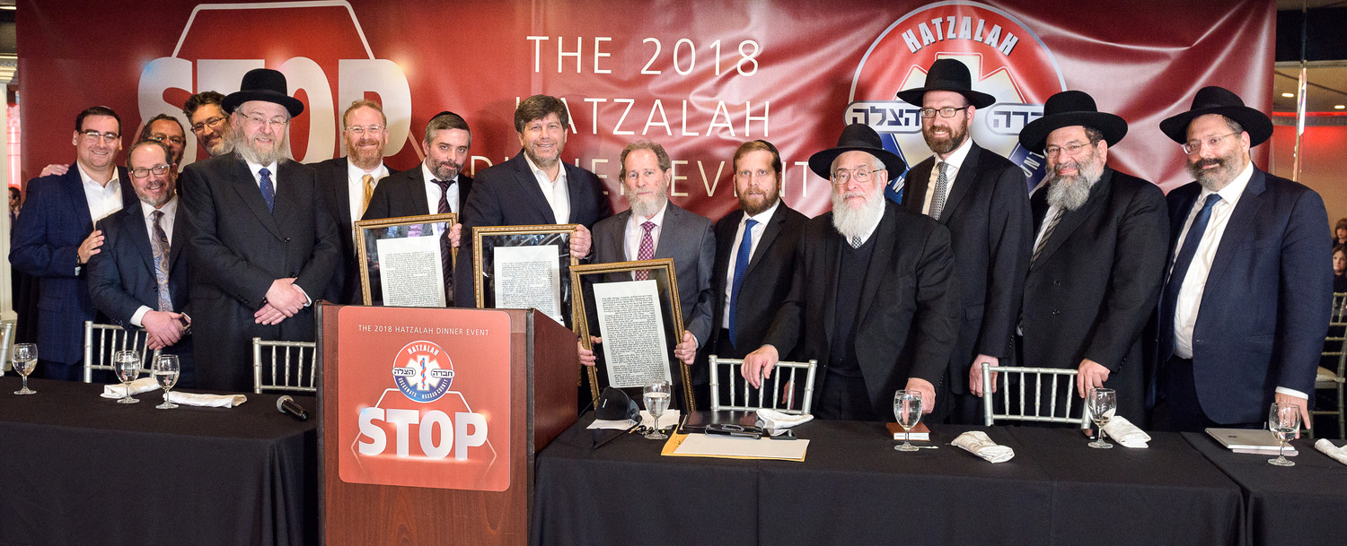Hatzalah members, officials and honoreesincluding (holding their plaques) Yechiel Zlotnick, Shea Farkas and Mike Krengel.
