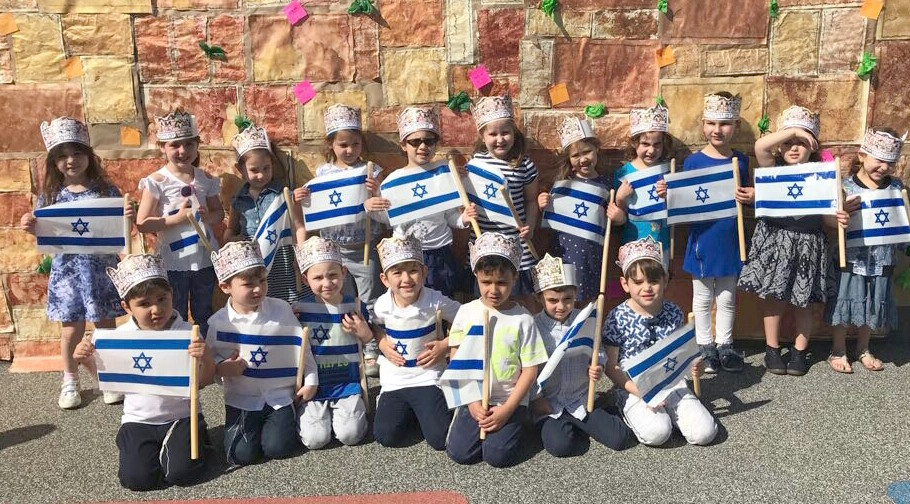 Flag-bearing HAFTR early childhood students posed in front of a mock-Kotel at their school.