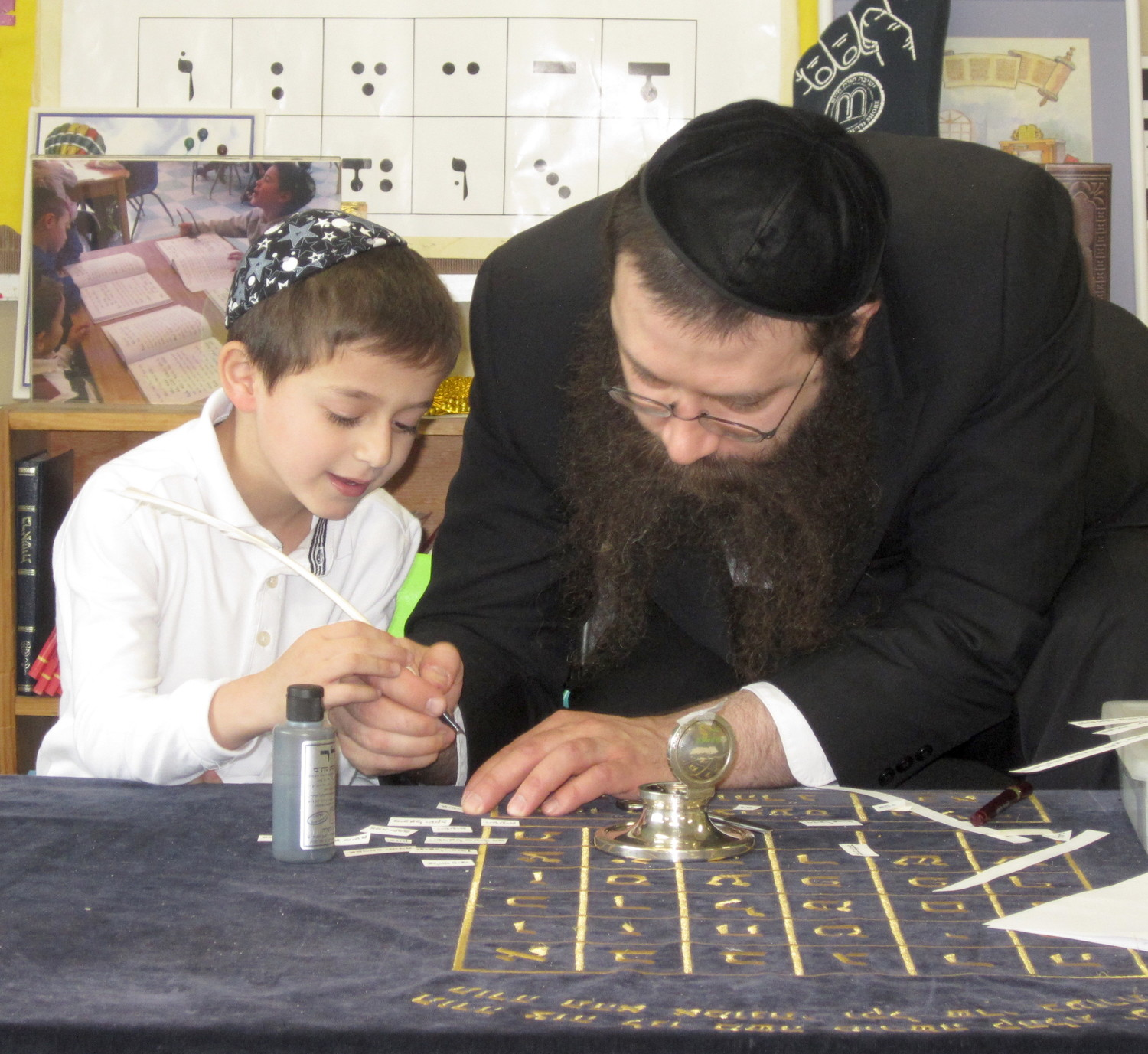 Asher Romer, a Pre-1A student at YOSS, is pictured with the sofer, Rabbi Betzalel Katkovsky.