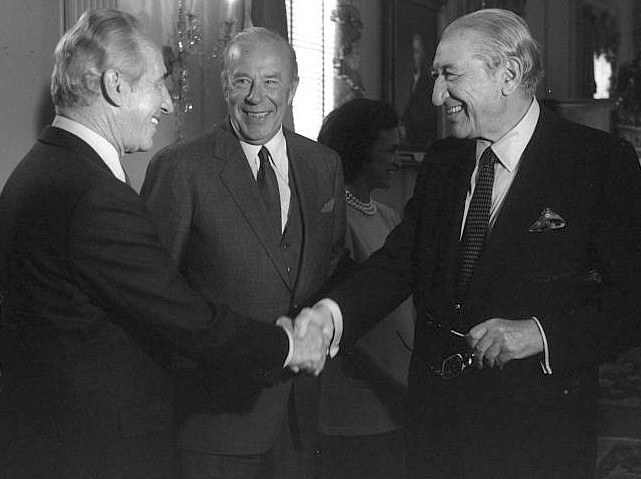 Israeli Prime Minister Shimon Peres (left) shakes hands with U.S. Jewish industrialist Max Fisher at a reception given by U.S. Secretary of State George Shultz (center).
