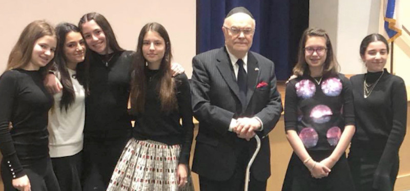 HALB eighth grade girls stand with Jack Rybsztajn, a 93-year-old survivor who lives across the street from the school's new Woodmere campus.