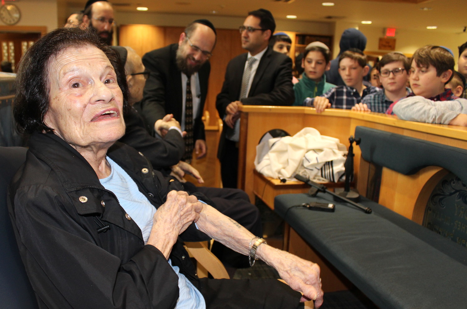 Holocaust survivor Dora Siegelman shows students at the Yeshiva of South Shore the numbers on her arm.