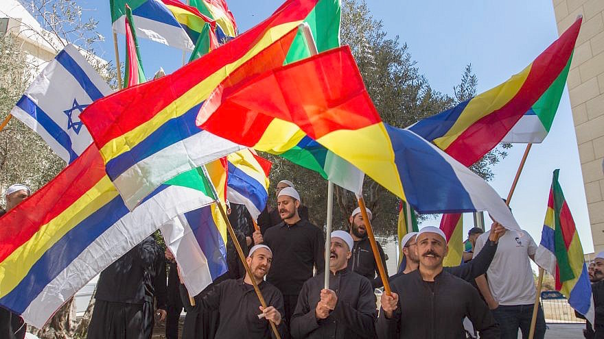 Druze men protest outside the Haifa District Court, carrying both the Druze and Israeli flags.