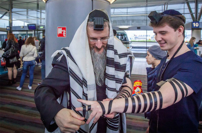 Russia's Chief Rabbi Berel Lazar helps a young man wrap the leather straps of tefillin during a trip to France in 2015.