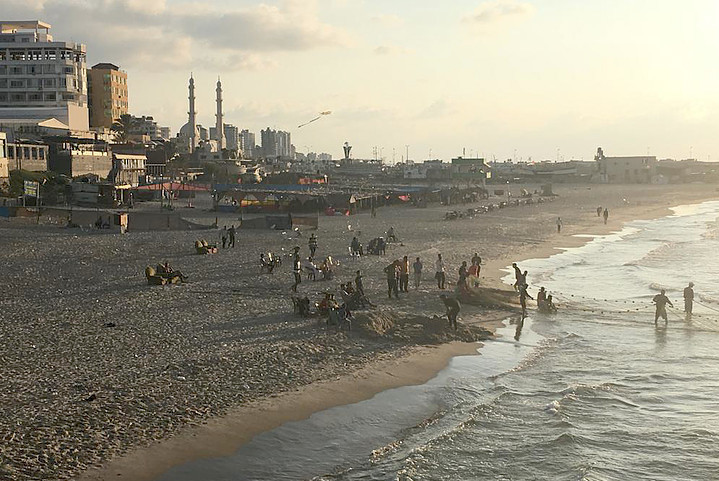 Gazans gather on a beach at sunset.