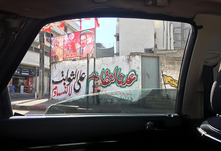 A PFLP poster is seen through the window of a passing car.