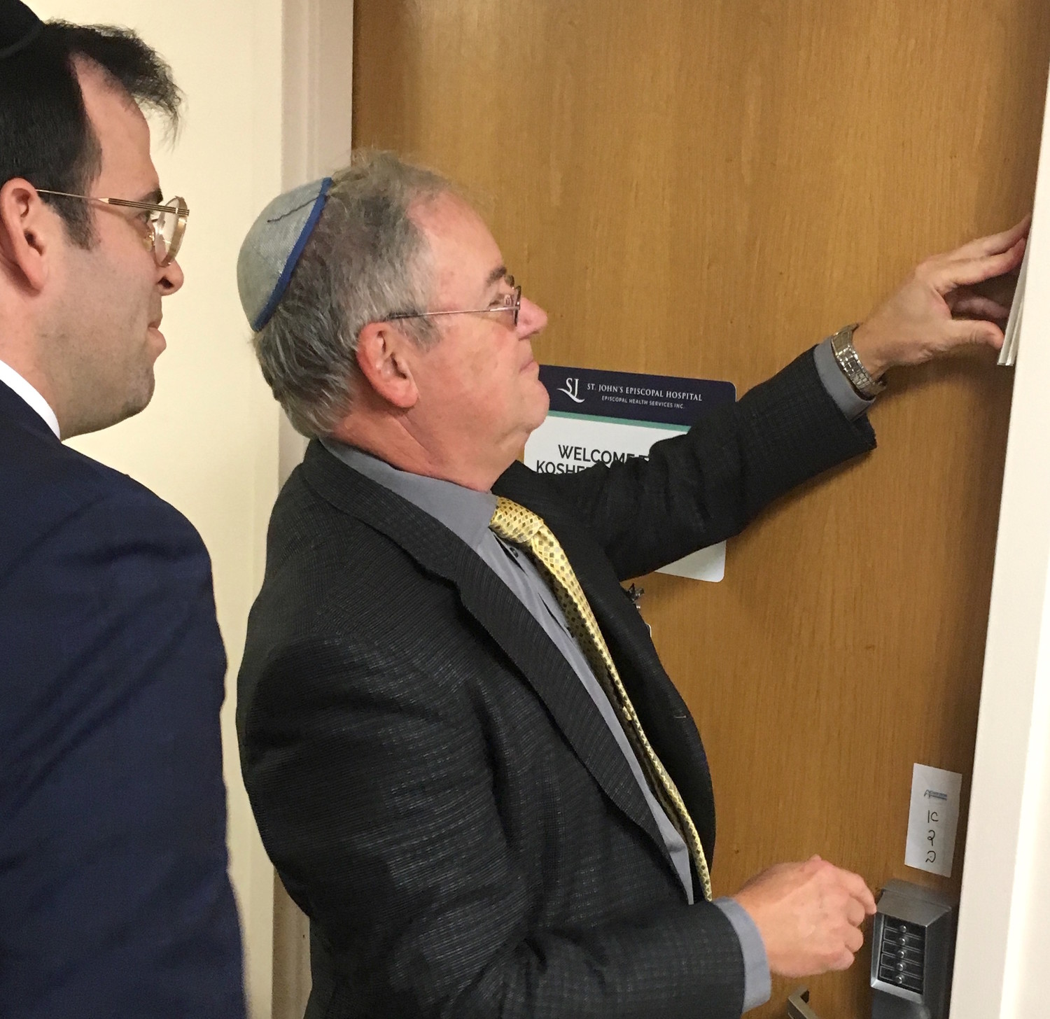 Dr. Nathan Rothman, flanked by Rabbi Boruch Ber Bender of Achiezer, hung the mezuzah.