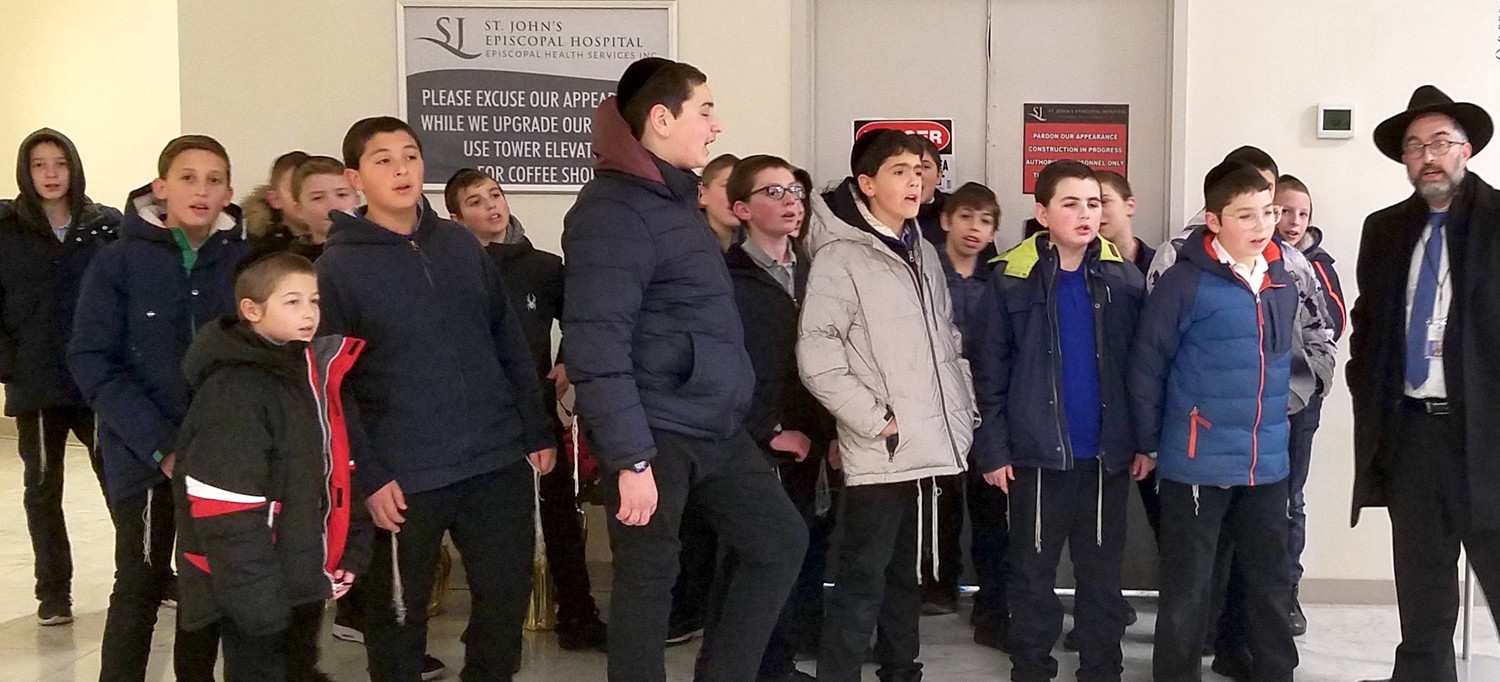 Rav Dovid Frischman and his seventh-grade talmidim at Yeshiva Darchei Torah brought the message of Chanukah to patients at St. John's Hospital in Far Rockaway.