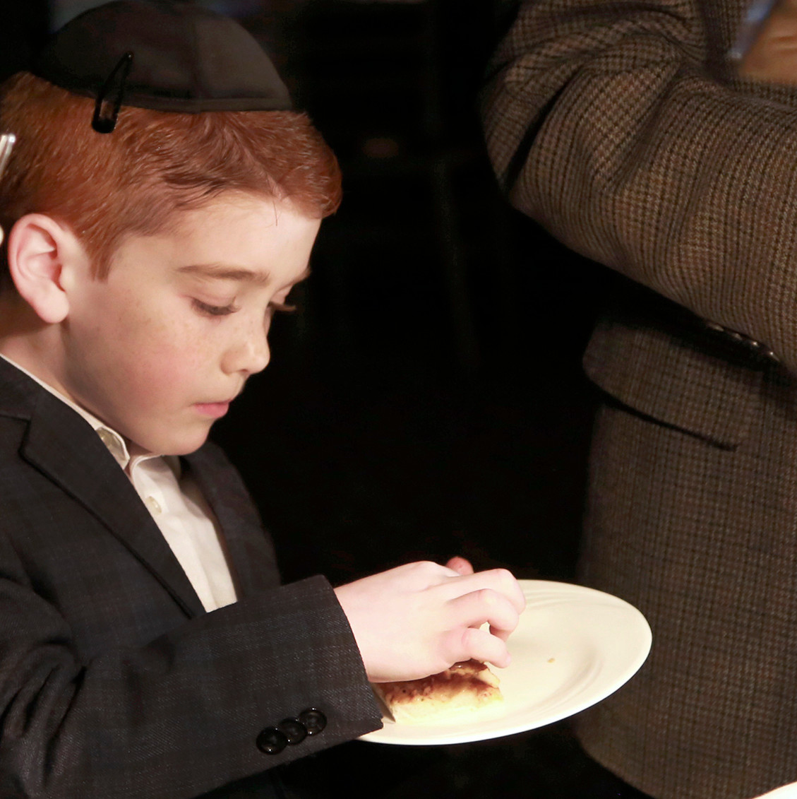 Seven-year old Levi Horshander, son of an awardee, samples focaccia bread.
