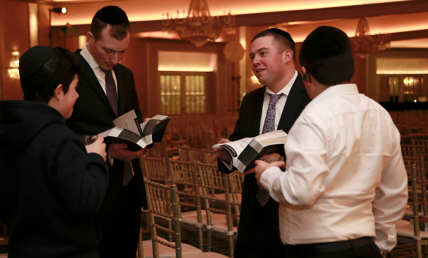 Yossi Riesman, Aaron Guttman, Harry Swambart and Dovid Barkinay browse the gala's journal, filled with 900 pages of ads placed by Achiezer supporters.