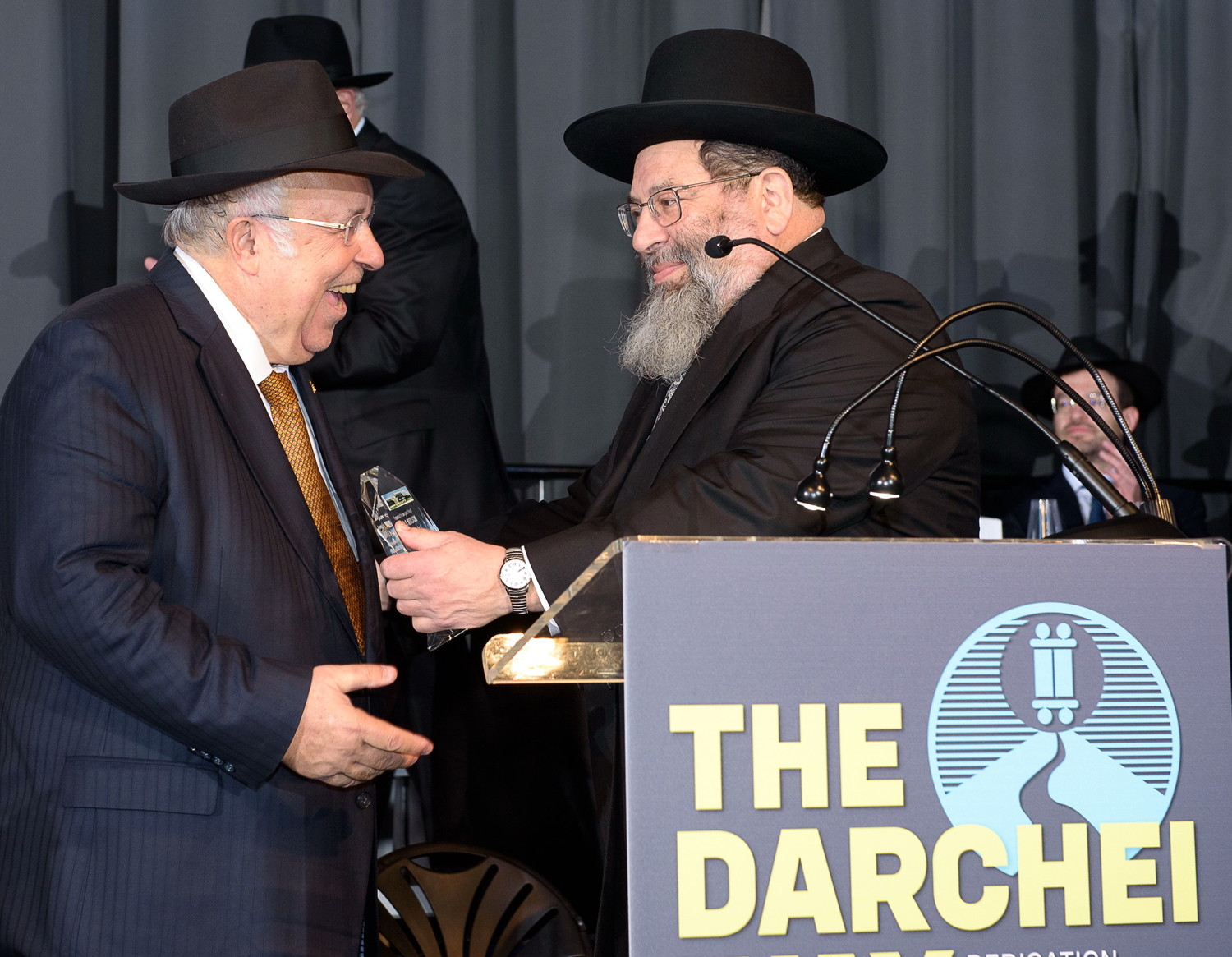 Rabbi Yaakov Bender makes a surprise presentation to Rabbi Lloyd Keilson, co-chairman of the YDT board, in recognition of his tireless efforts on the school's mortgage refinance.
