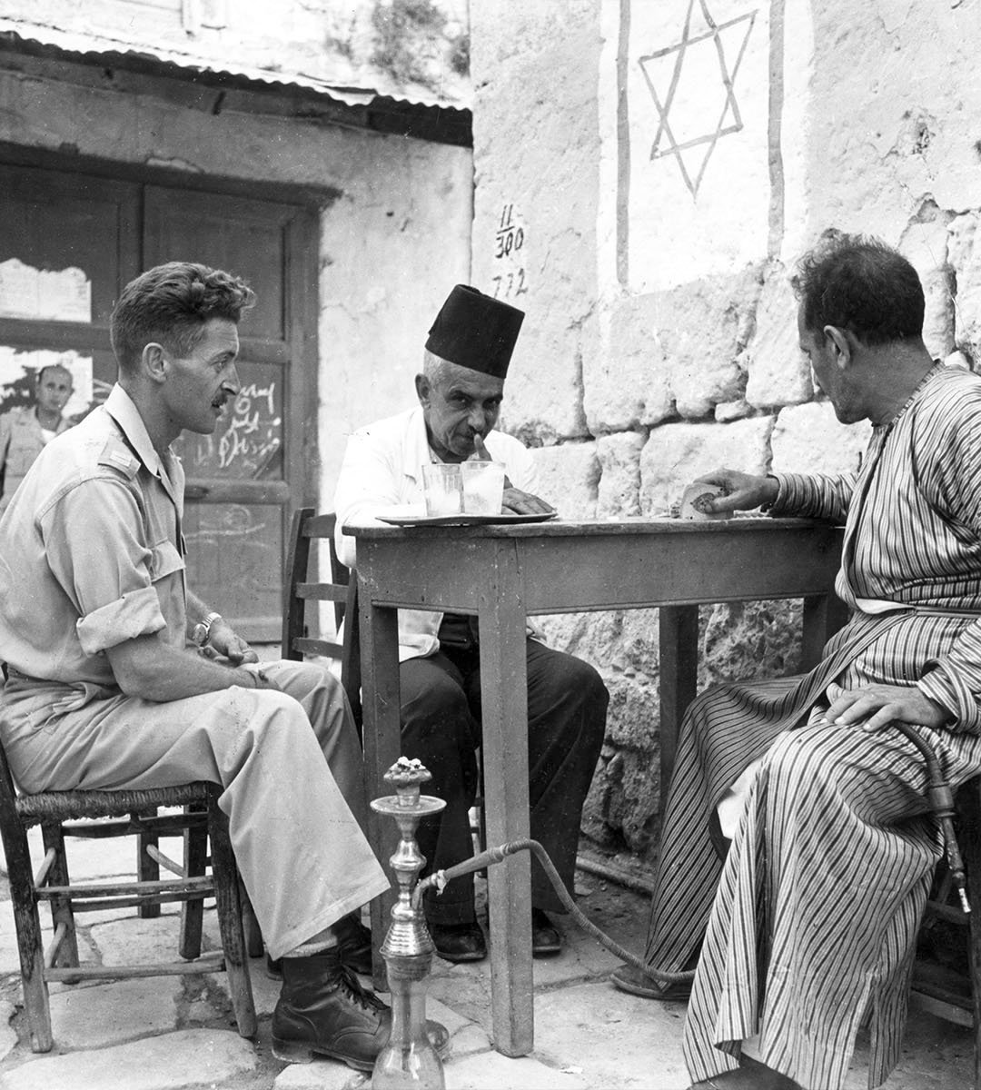 A Jewish soldier and two Arab tradesmen enjoy a game of cards in the town of Madjdal at the entrance to the Negev, 1937.