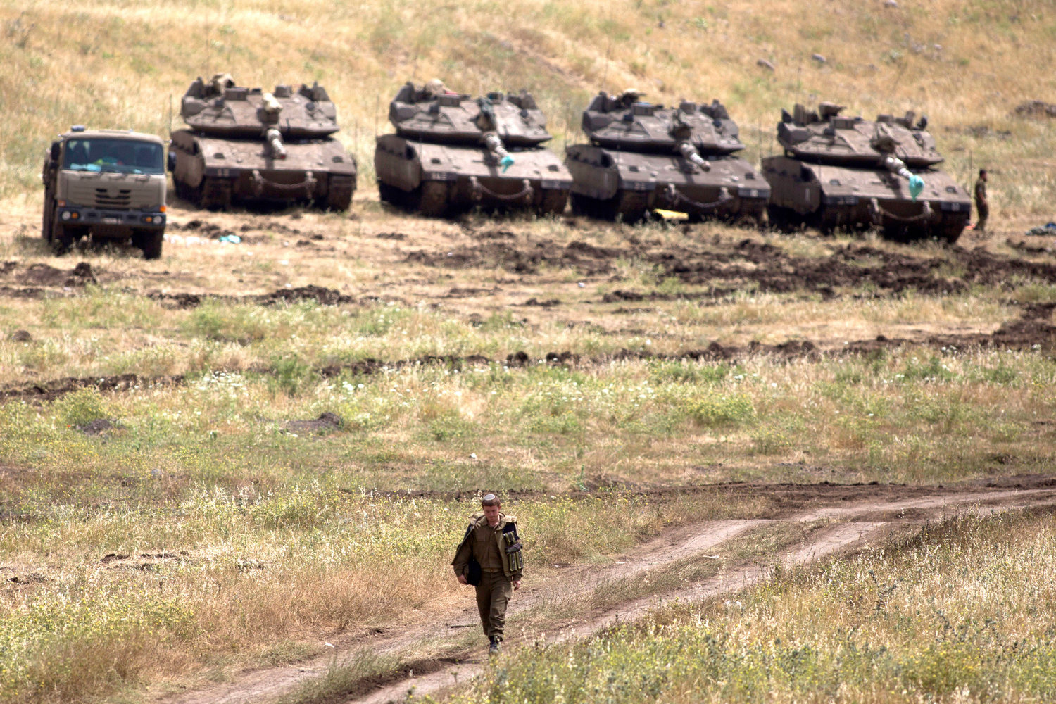 An Israeli soldier walks next to Merkava tanks deployed near the Israeli-Syrian border on May 10, 2018 in the Israeli-annexed Golan Heights.