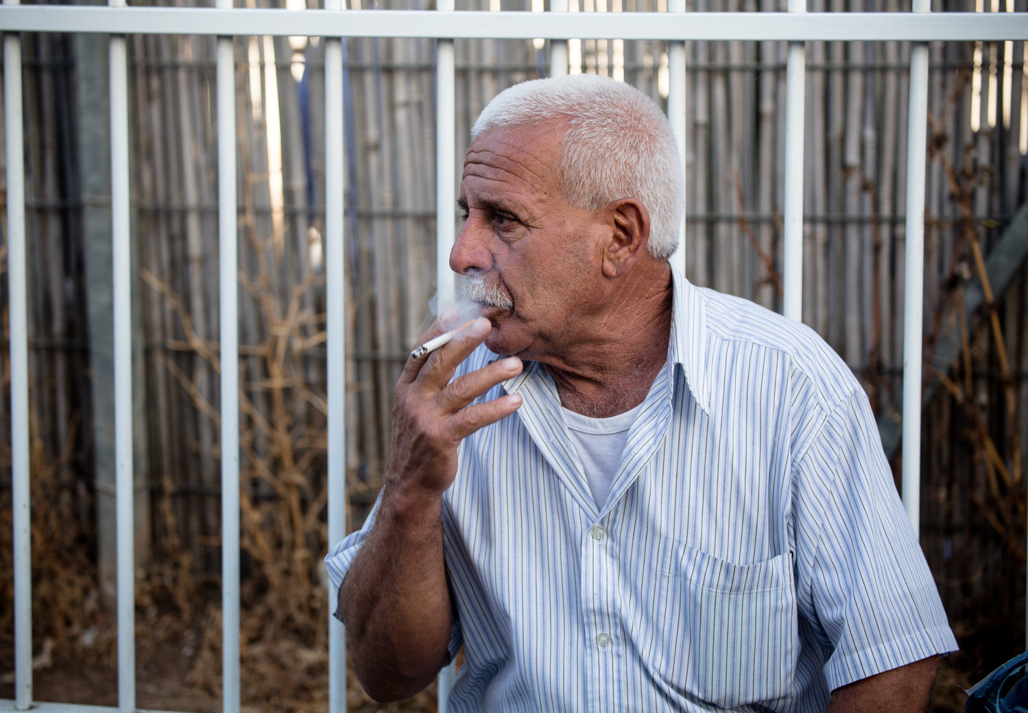 A Palestinian man smokes a cigarette at the Checkpoint 300 border crossing into Israel.