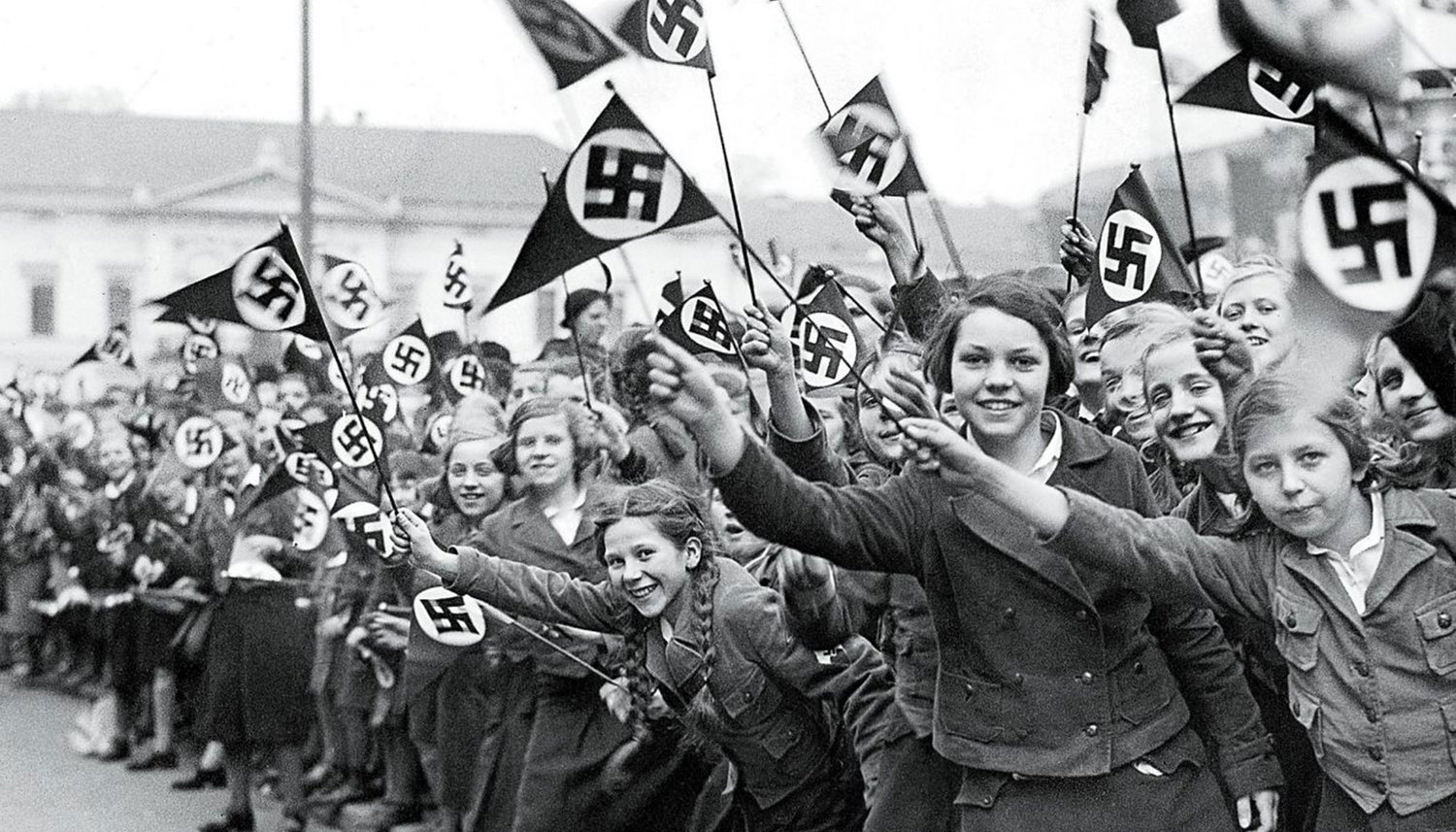 Members of the League of German Girls wave Nazi flags in support of the German annexation of Austria, in Vienna, March 1938.