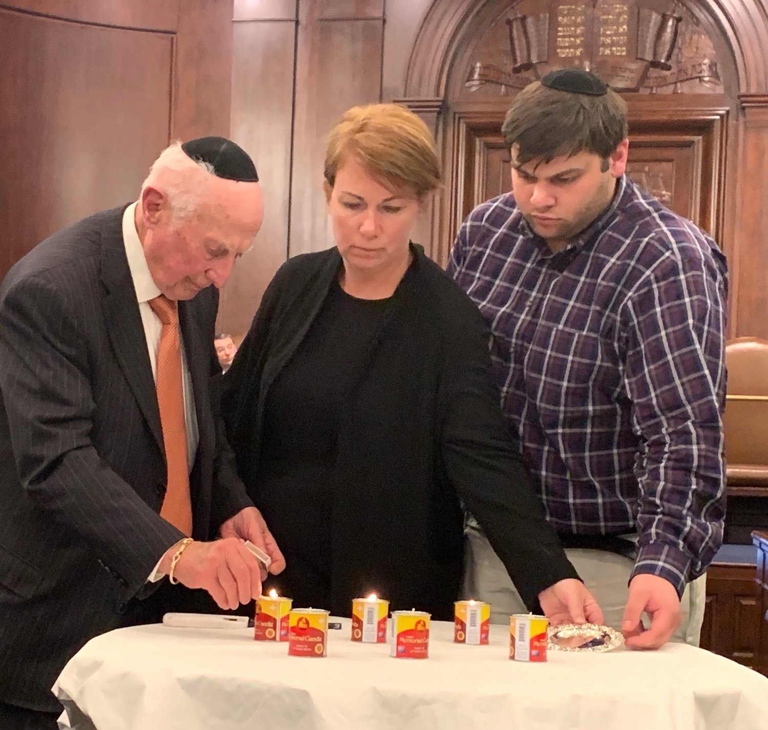 Survivor Frank Berger lights a memorial candle at Five Towns Holocaust remembrance event, at Congregation Beth Sholom in Lawrence, March 1, 2019.