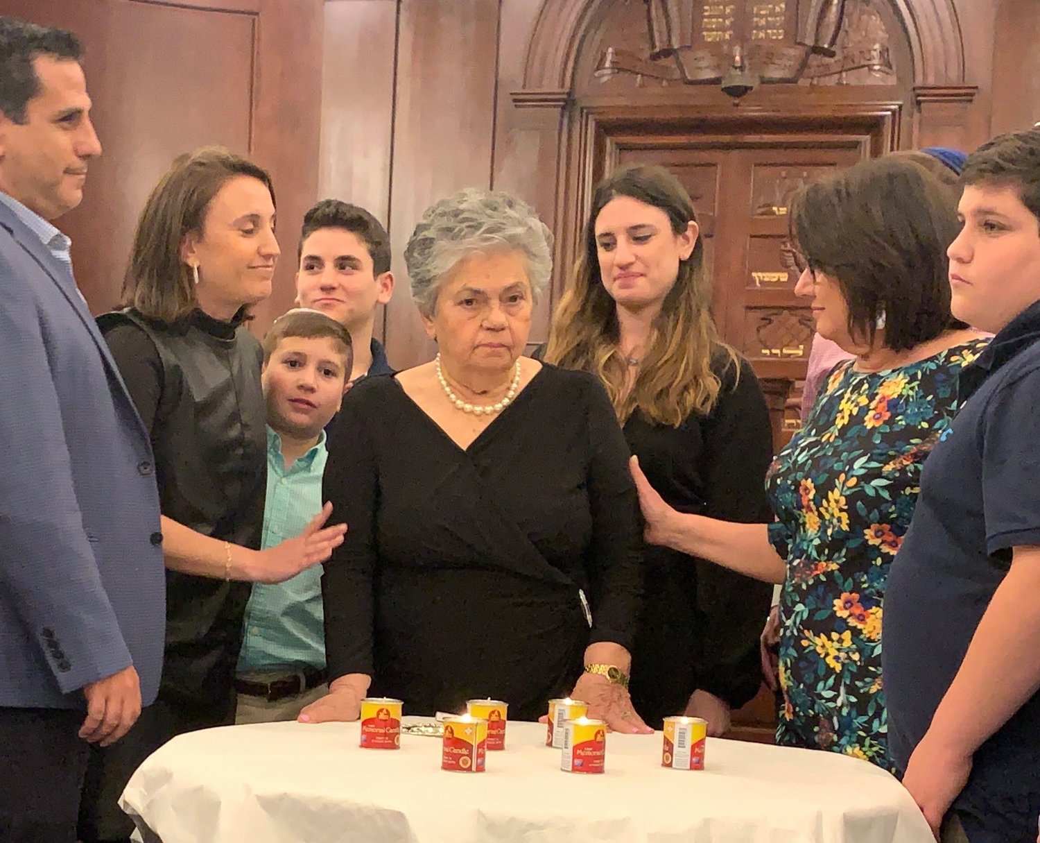 Survivor Luba Schulsinger lights a memorial candle at Five Towns Holocaust remembrance event, at Congregation Beth Sholom in Lawrence, March 1, 2019.