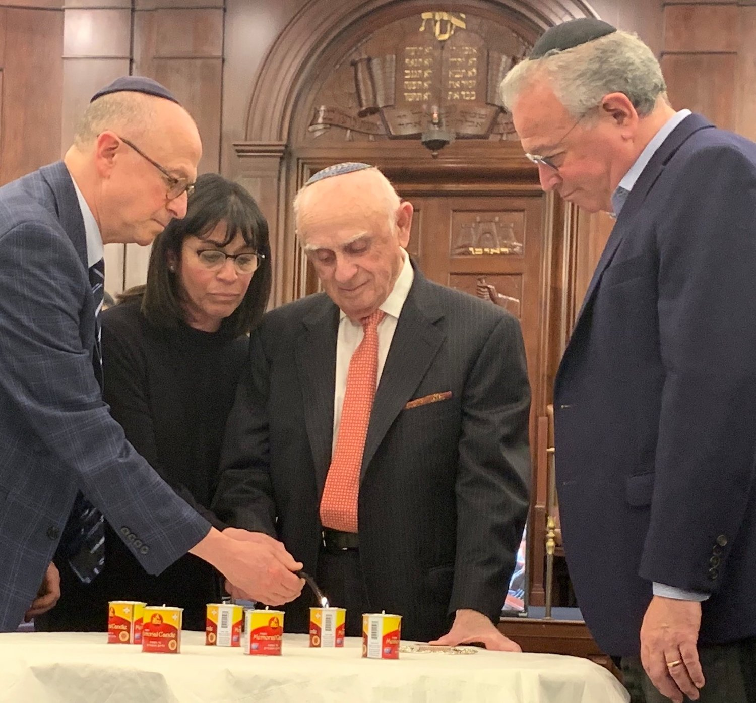 Survivor Mel (Mendel) Klapper lights a memorial candle at Five Towns Holocaust remembrance event, at Congregation Beth Sholom in Lawrence, March 1, 2019.