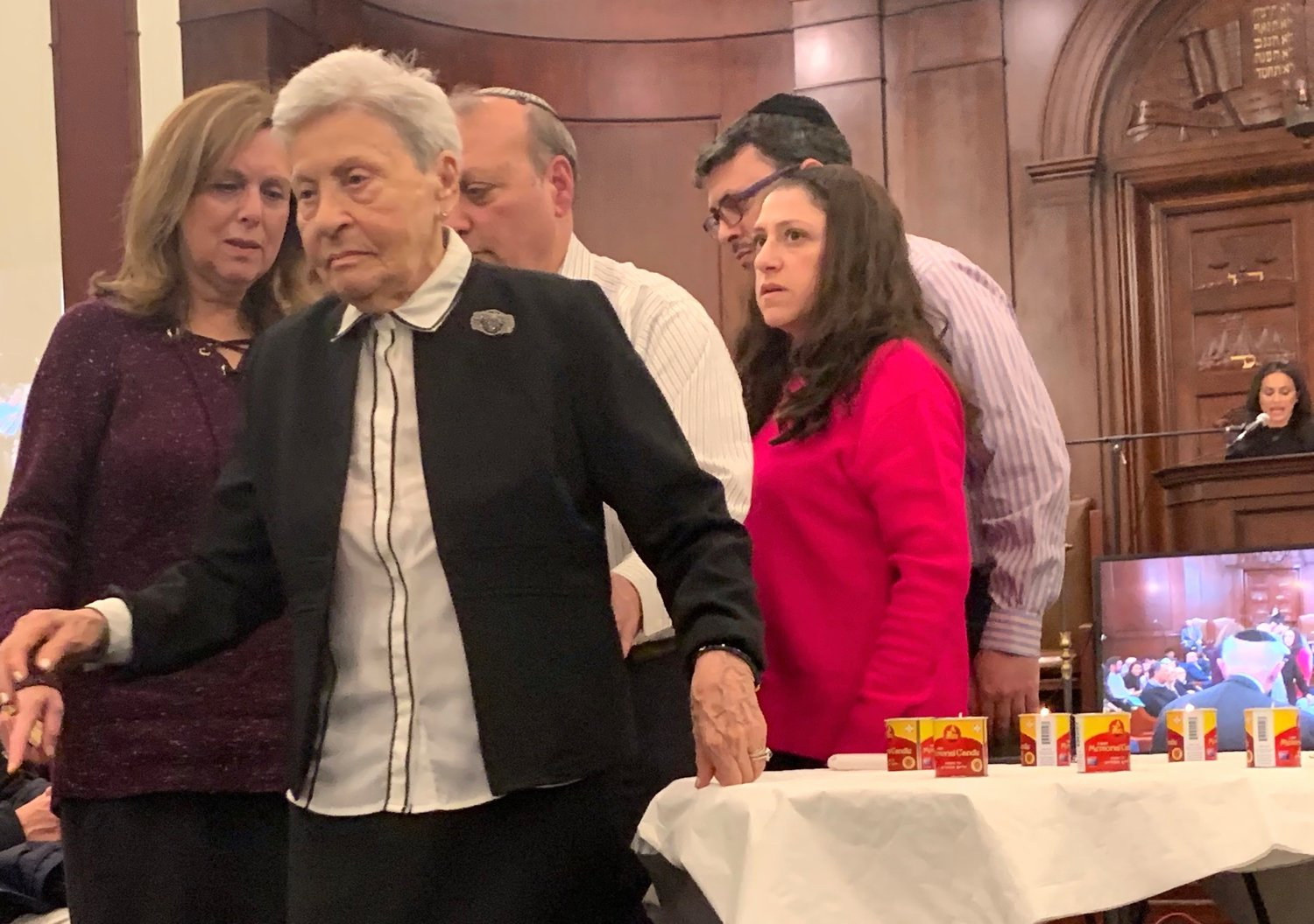 Survivor Natalie Gomberg lights a memorial candle at Five Towns Holocaust remembrance event, at Congregation Beth Sholom in Lawrence, March 1, 2019.