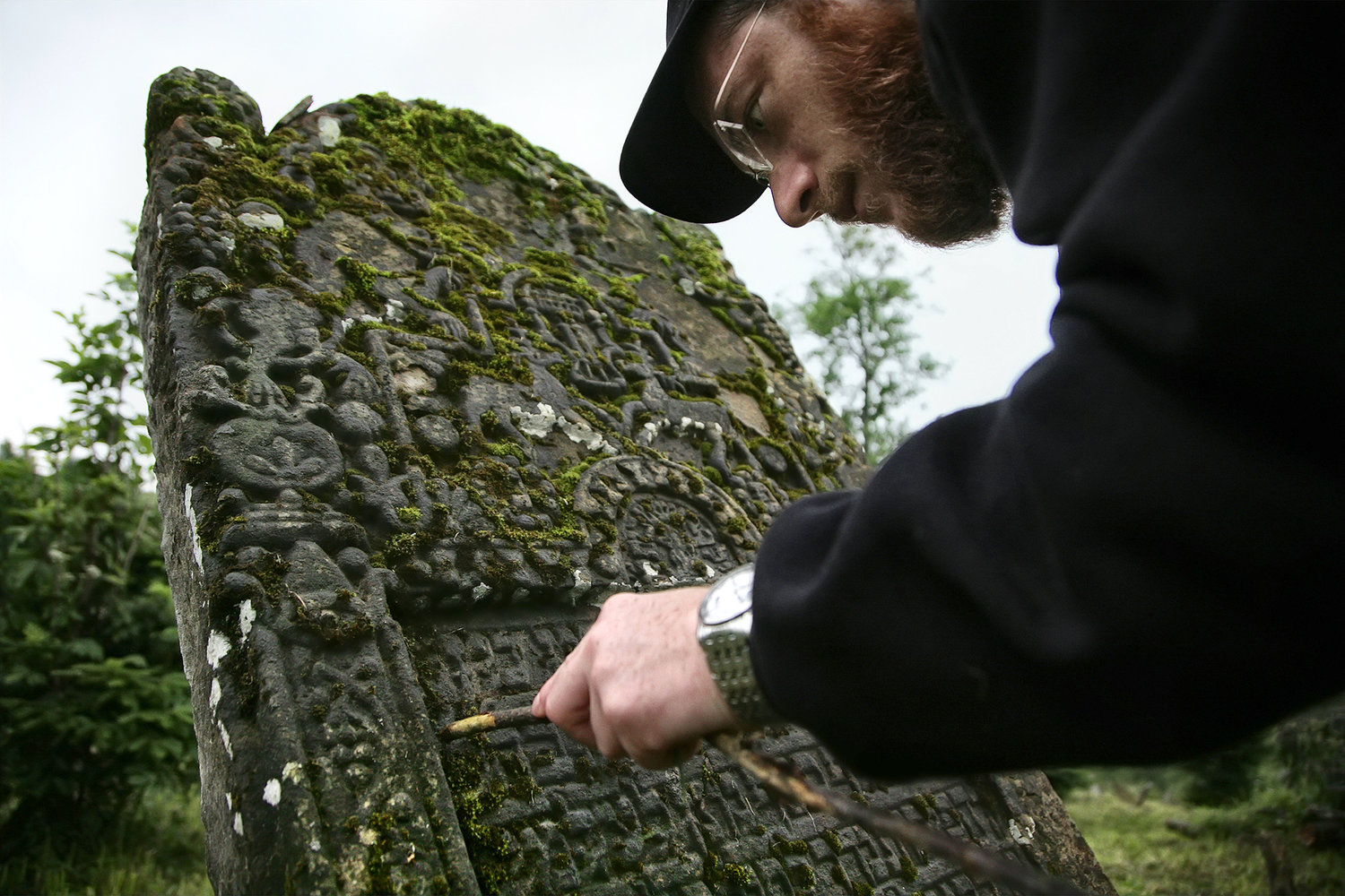 Yaakov Lemmer, a Hasidic cantor from Brooklyn, cleans off a tombstone at a cemetery in Jasliska, Poland.
