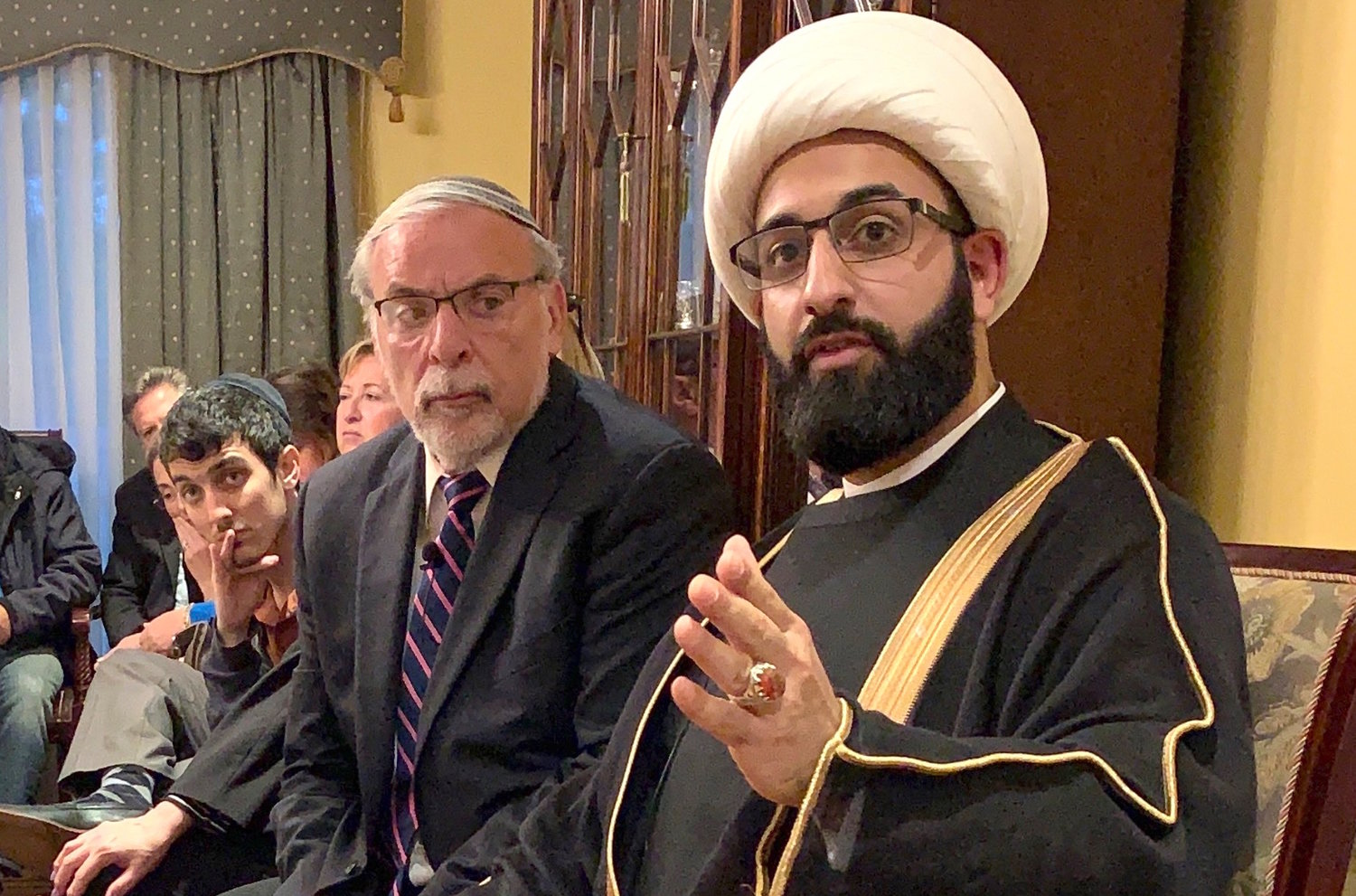 Imam Mohammad Tawhidi speaks, flanked by former Assemblyman Dov Hikind, at a parlor meeting in Woodmere.