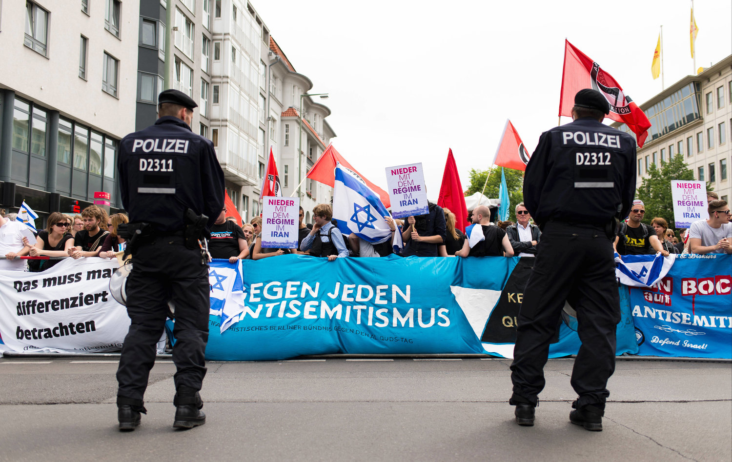 "Demonstrators carry a banner that reads ""Against any kind of anti-Semitism"" during a rally against the annual al-Quds Day march in Berlin on July 11, 2015. Anti-Israel rallies are held annually on the day."