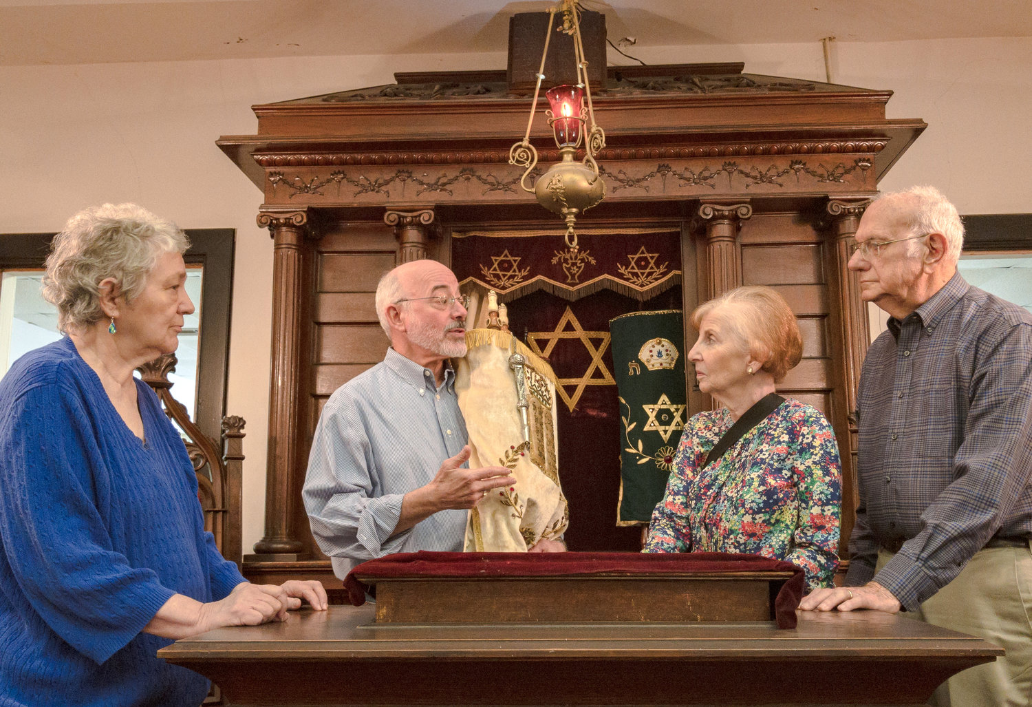 Temple Mishkan Israel in Selma, Ala., and its four members (from left) Hanna Berger, Ronnie Leet, Joanie Gibian Looney and Charles Pollack, in front of the Torah ark.