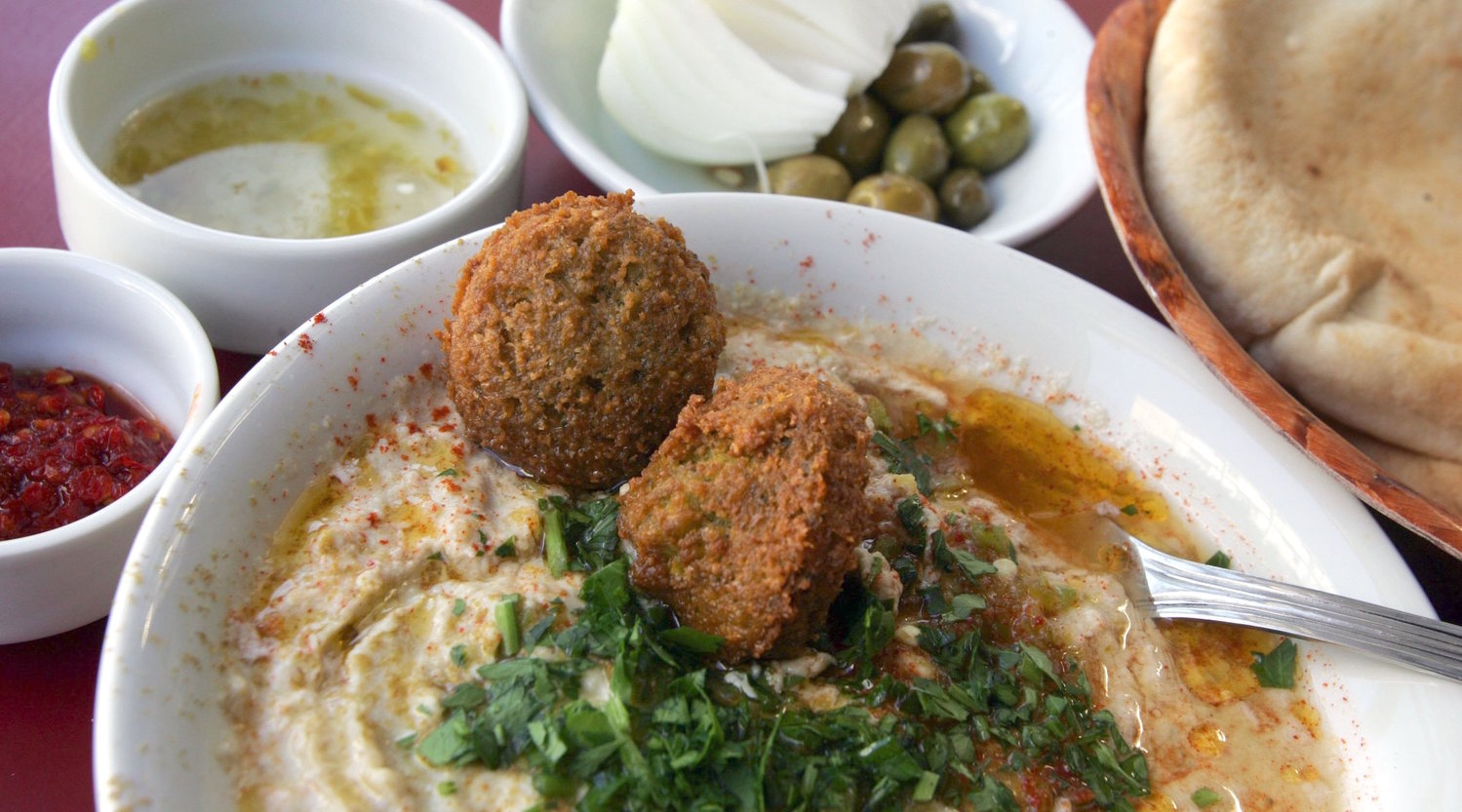 A bowl of hummous is served with olive oil, falafel balls and sprinkled with chopped parsley alongside fresh-baked pita bread, olives, a fresh onion, red chili paste and chili and lemon juice in a restaurant in Tel Aviv.