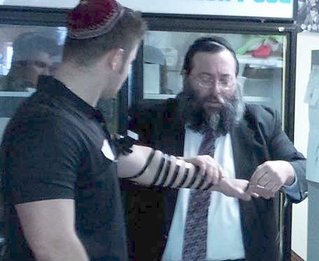 Rabbi Yossi Jacobson helps a customer wrap tefillin in his Maccabees Kosher Deli in Des Moines, Iowa.