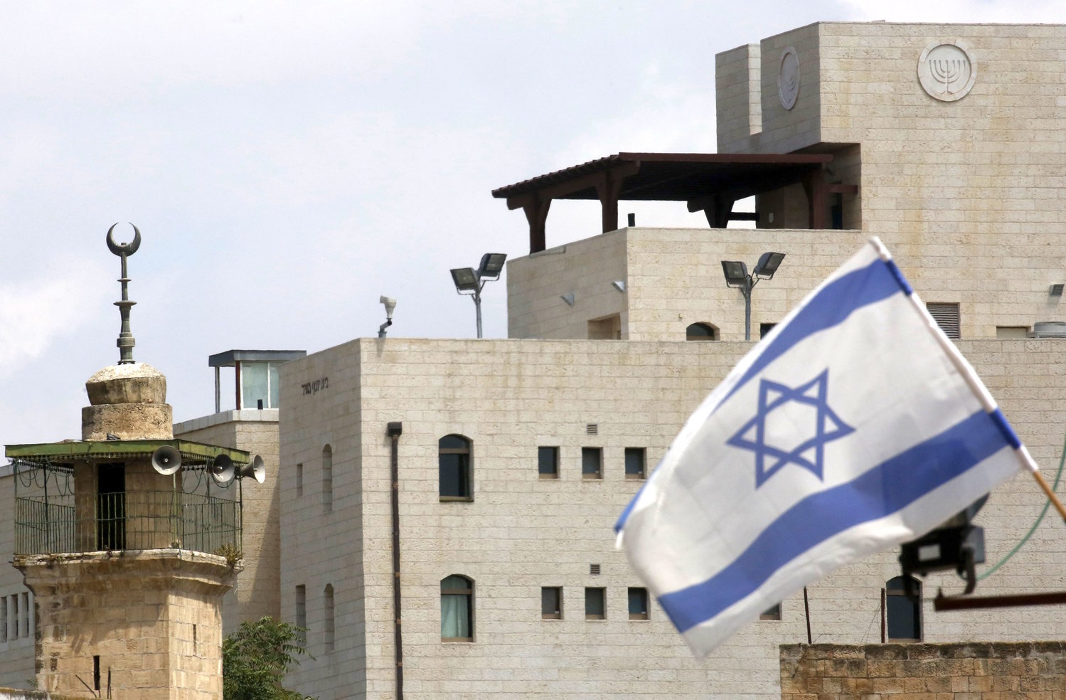 An Israeli flag in the small Hebron Jewish community, near the minaret of a mosque.