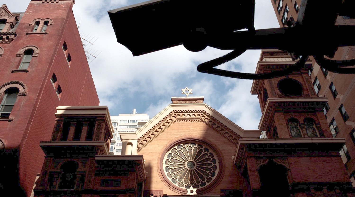 A security camera hangs across the street from the Park East Synagogue in Manhattan.