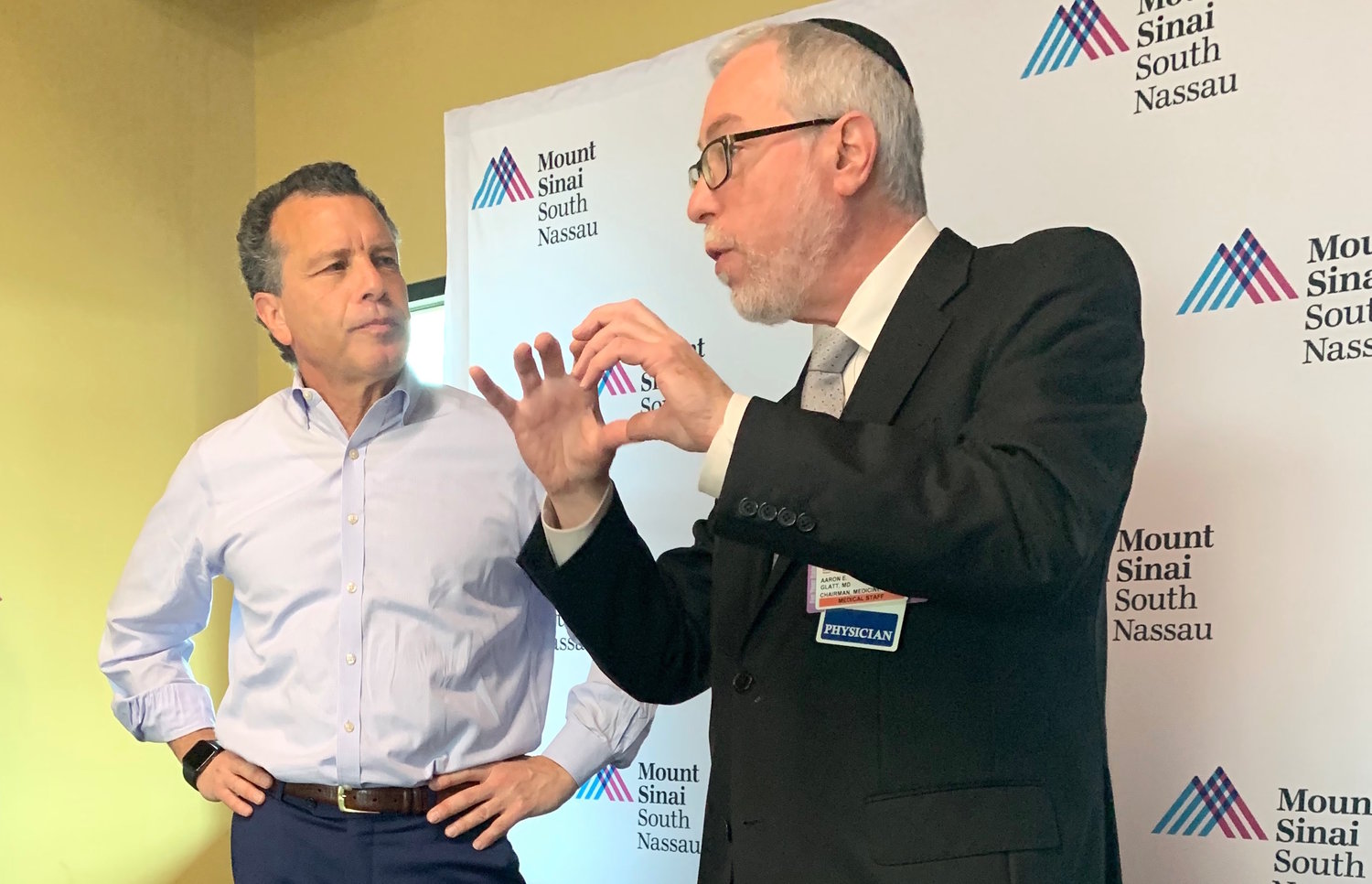 Richer Communications President Stuart Richner listens as Rabbi Dr. Glatt addresses Richner employees about the importance of being immunized.