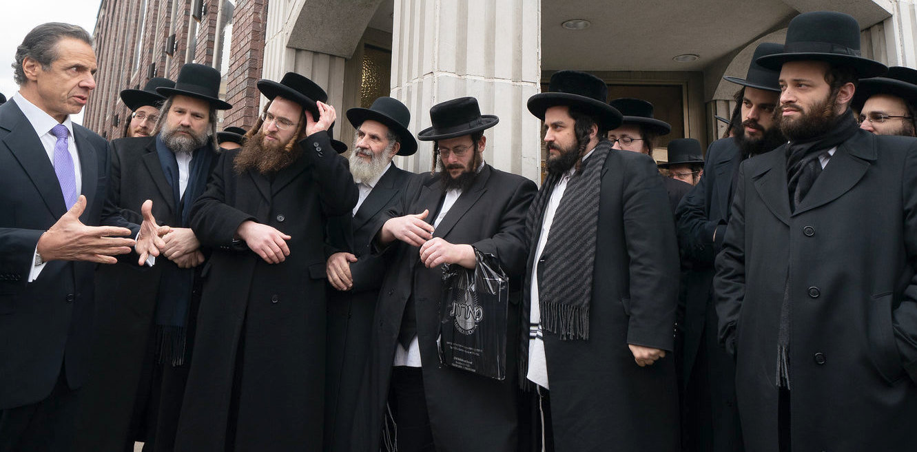 Gov. Andrew Cuomo speaking with men outside a shul in Brooklyn's Williamsburg neighborhood.