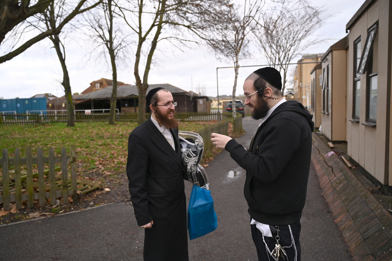 Jacob Gross, right, speaks to a Canvey Island resident outside the town's synagogue on Dec. 13.