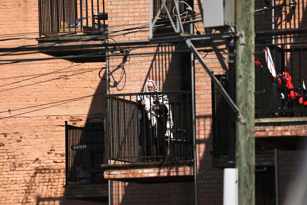 A man prays on his balcony in Brooklyn on April 25.