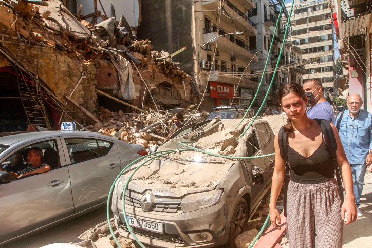 Pedestrians and motorists on one of the many devastated streets in Beirut, Lebanon, on Aug. 5 the day after a massive deadly explosion shook the city.