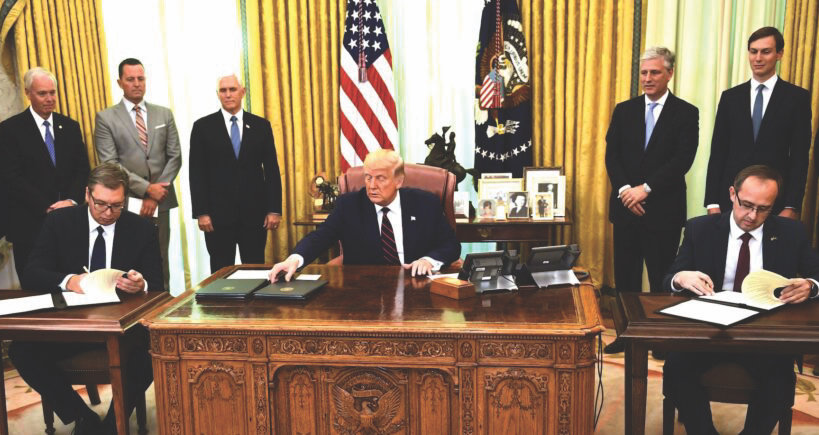 President Donald Trump watches as Kosovar Prime Minister Avdullah Hoti (right) and Serbian President Aleksandar Vucic (left) sign an agreement on opening economic relations, in the Oval Office on Sept. 4.
