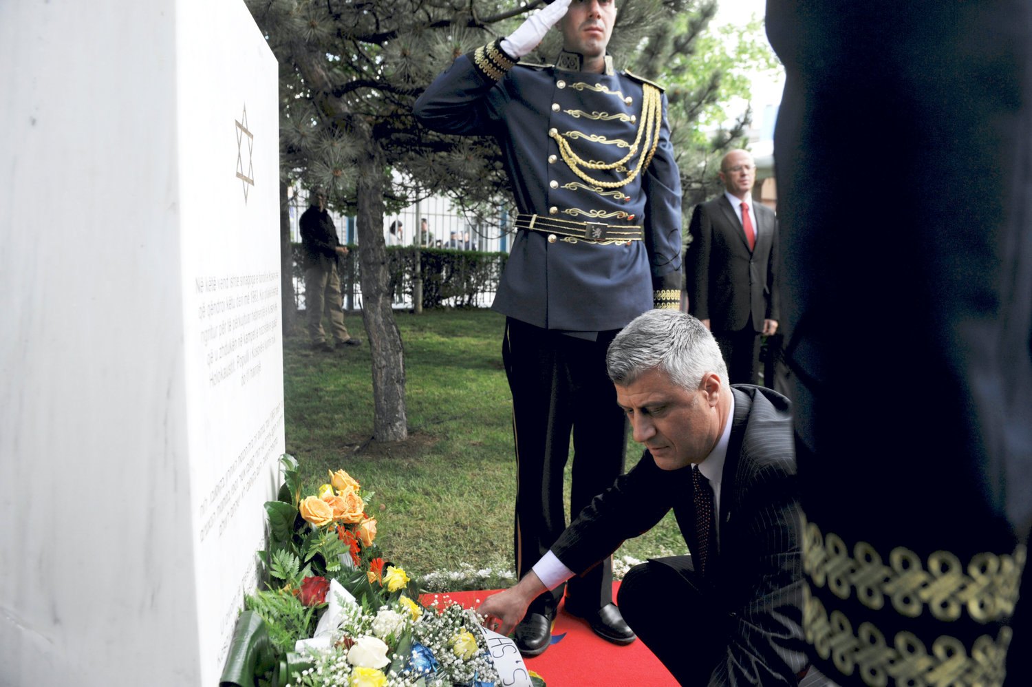 Kosovo Prime Minister Hashim Thaci places flowers in Pristina, May 23, 2013, on the commemorative plaque remembering Kosovo Jews who perished in the Shoah, at the site where the last synagogue of Kosovo stood until 1963.