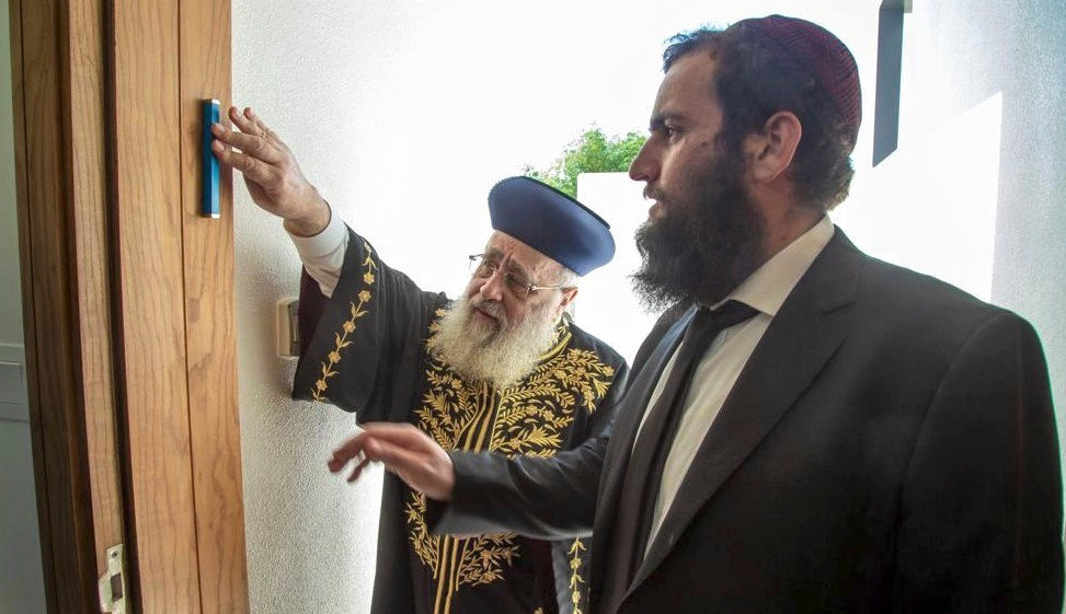 Israel's Chief Sephardic Rabbi Yitzhak Yosef affixes a mezuzah to a doorpost of the newly built Jewish school in the United Arab Emirates while on his first trip to an Arab country, as Chabad Rabbi Levi Duchman of the UAE looks on.