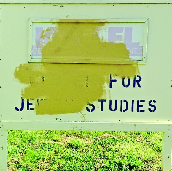 The sign with the vandalism obscured.