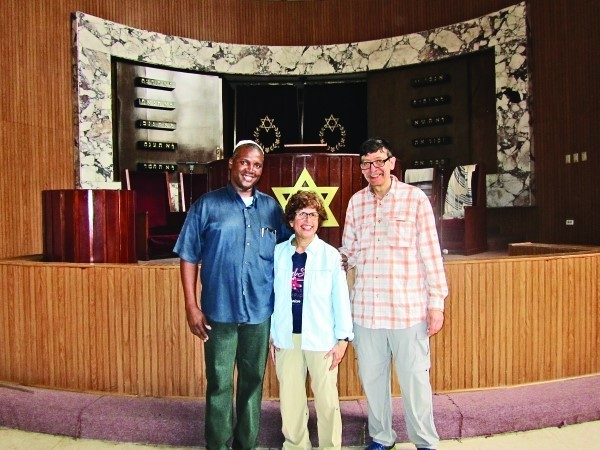 Lynne Glickman, Mark Kanter with their guide in front of the  bimah at Temple Beth Shalom in Havana.