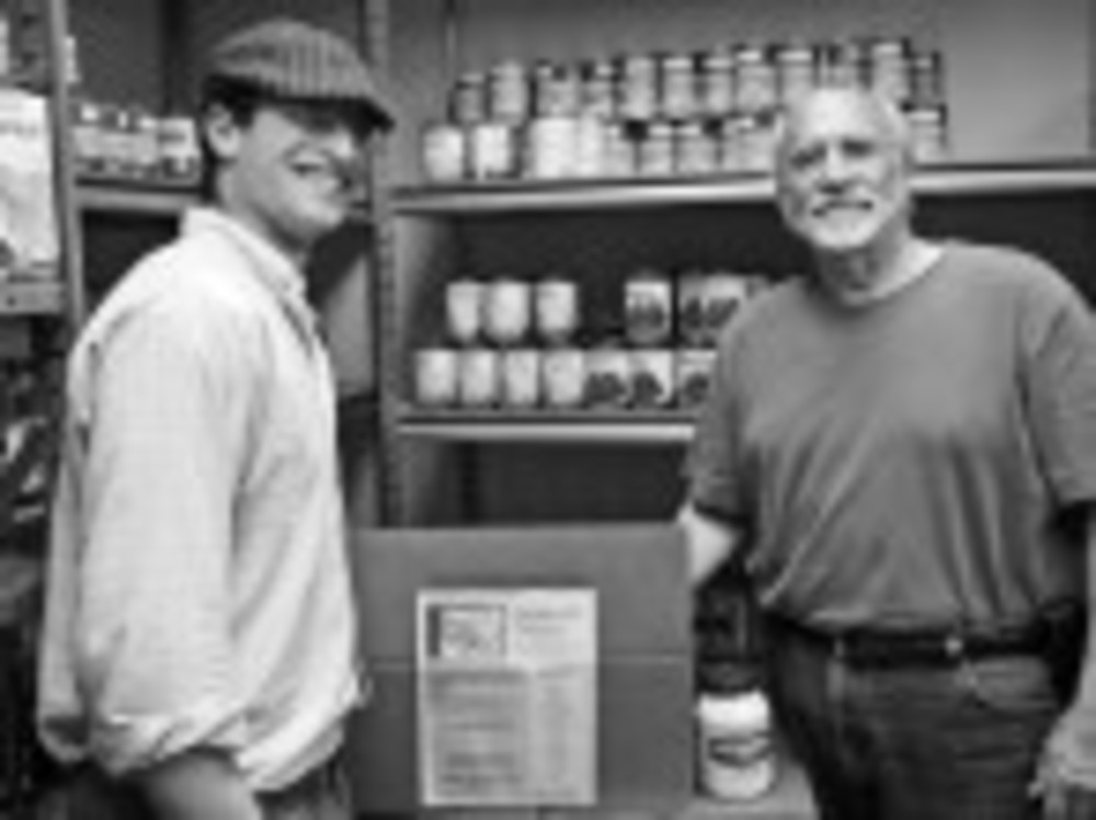 Sugarman-Sinai's Nozzi Gerstman, left, and Ira Fleisher stand by shelves stocked with donated food.  /Susan Adler