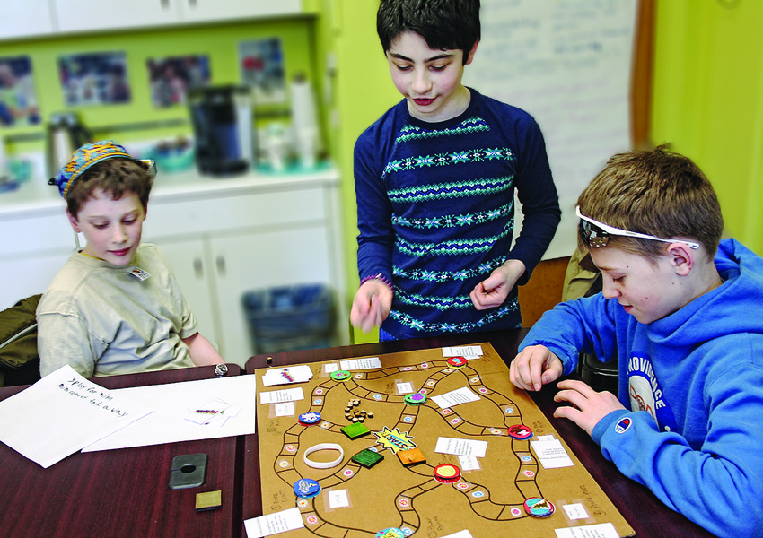 Fifth graders at JCDSRI work on test games   provided by Brown University students.