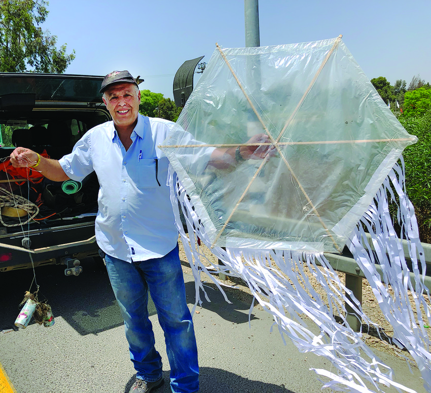 """An Israeli holds a """"terror kite""""   and the incendiary materials attached to it"""