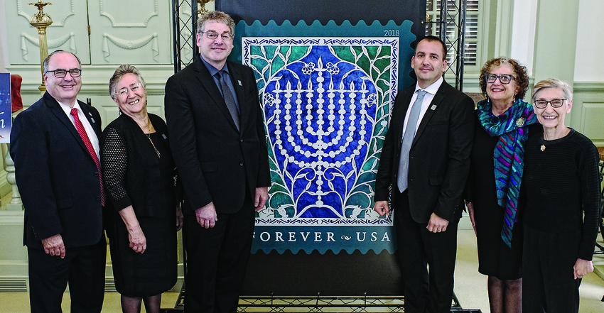 At the unveiling of the new Hanukkah stamp in Newport (left to right): David D. Mastroianni, Jr., Postal Service Connecticut Valley district manager served as the master   of ceremonies;Tamar Fishman created the original art for the stamp;Postal Service   Judicial Officer Gary Shapiro gave the address;Elhanan Shapira, Israel Post Philatelic Service director represented the Israeli government;Ethel Kessler, stamp designer and   Bea Ross, chair of the Touro Synagogue Foundation.