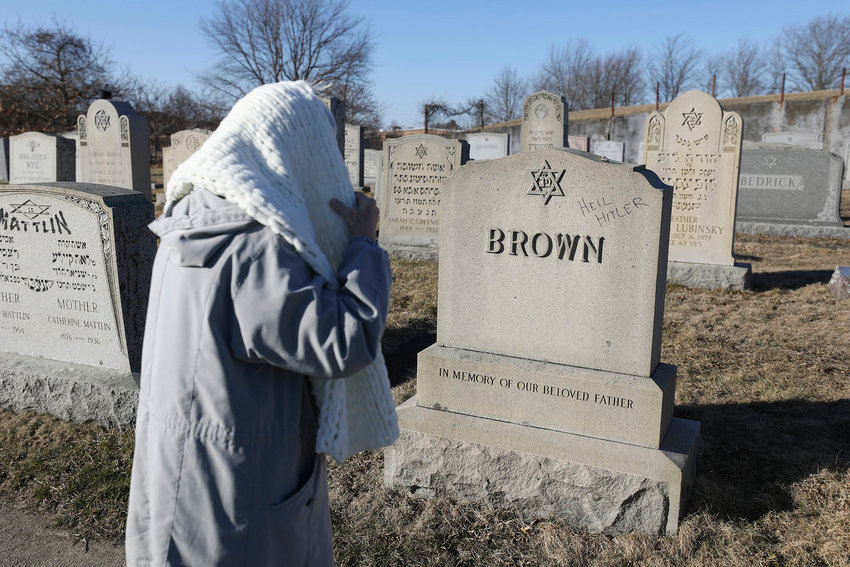 A woman stops to look at a vandalized  grave stone in the cemetery.