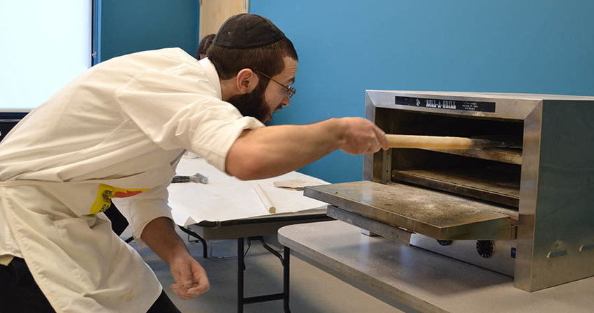 The matzah goes in the oven at the recent Matzah Factory at the Dwares JCC.
