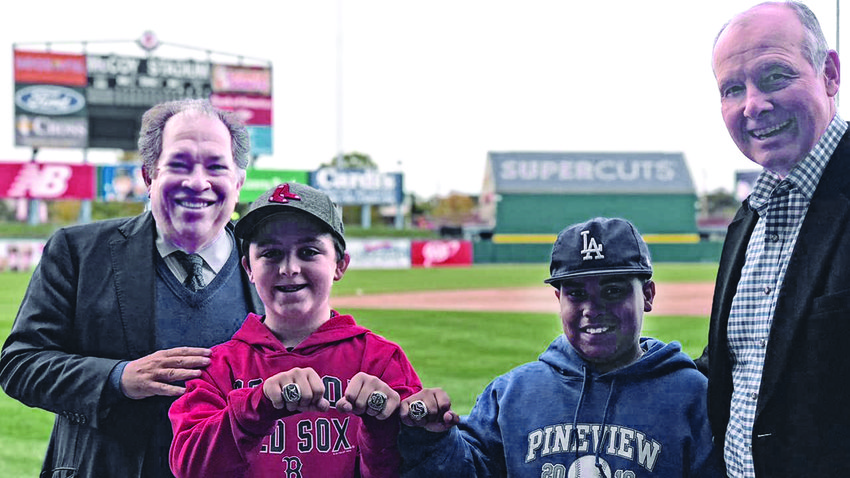 Pawtucket Red Sox President Dr. Charles Steinberg, left, and PawSox Vice Chairman and member of the team ownership group Mike Tamburro pose with two youngsters from the Pawtucket Boys and Girls Clubs who went to the World Series last October thanks to the PawSox.