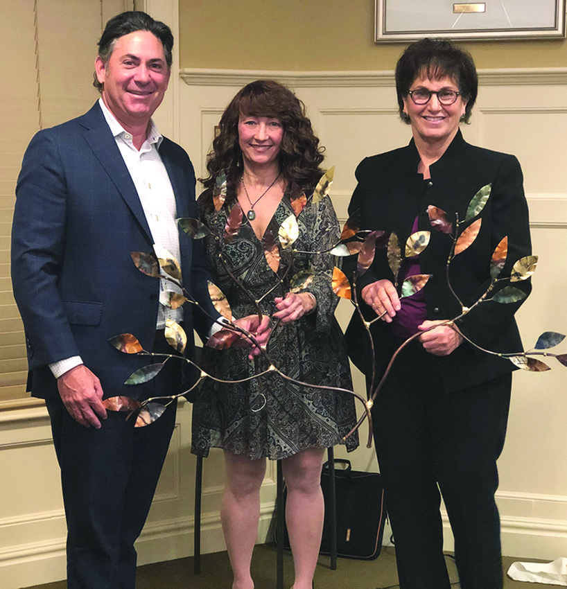 "Jeff Padwa, outgoing board chairman of Jewish Collaborative Services, poses with Marisa Garber, incoming JCS board chair, and JCS President and CEO Erin Minior after the JCS annual meeting, held at The Phyllis Siperstein Tamarisk Assisted Living Residence, in Warwick, on Nov. 5. They are holding a ""Tree of Life,"" a gift from JCS to Padwa for his years of service."