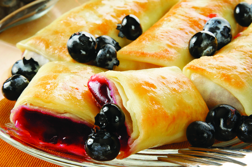 Closeup of golden blueberry blintzes or crepes with fresh berries